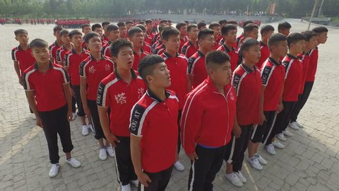 SHAOLIN, CHINA - MAY 2016: Kung fu students sing a song at the start of a training session on the grounds of a Shaolin martial arts school in central China