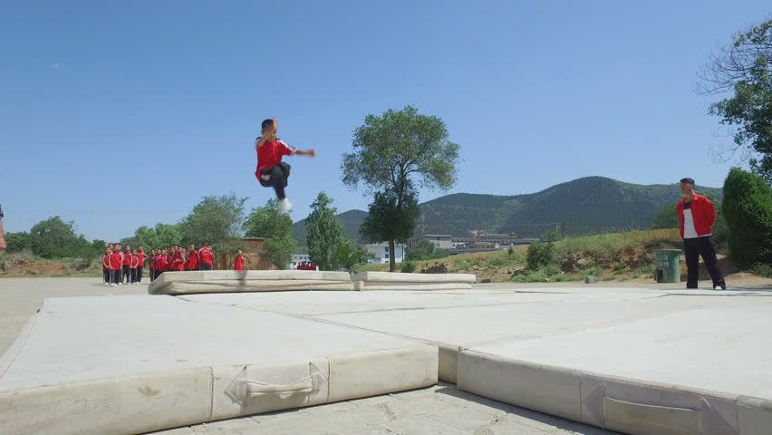 SHAOLIN, CHINA - MAY 2016: Young kung fu students make backflips at a martial arts institute in Shaolin, the 'birthplace' of kung fu, in central China