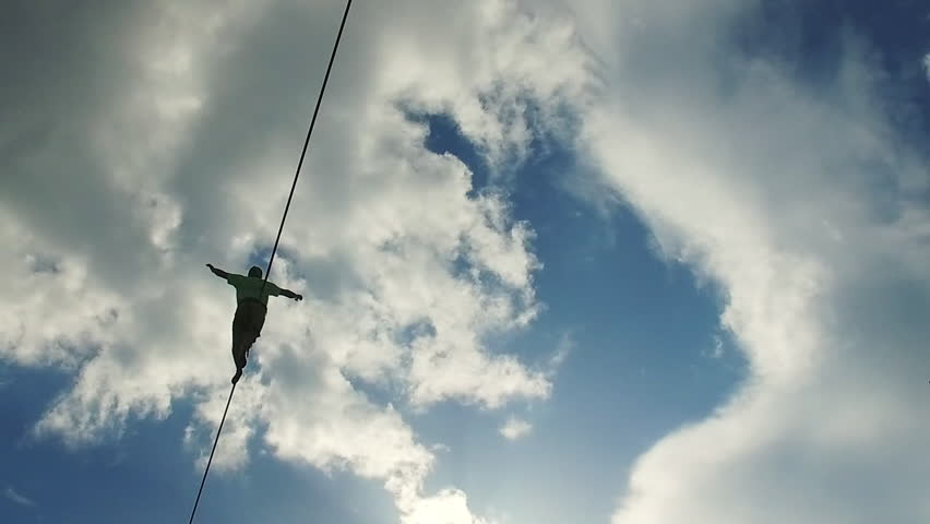 Young man walking on slackline with clouds background