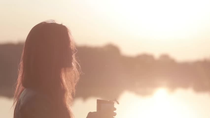 close-up portrait attractive young girl looks at the sunrise on the river and drinking coffee from a thermocup