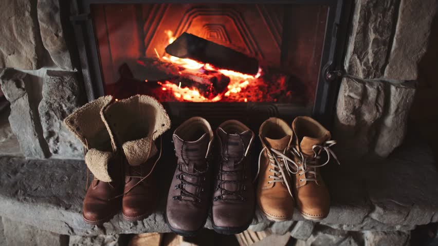 Winter boots in front of a fireplace 4K. Family vintage folk boots drying near the fireside. Warm cozy fireplace in the authentic chalet. Hipster shoes getting warm near the burning fire in a cabin.