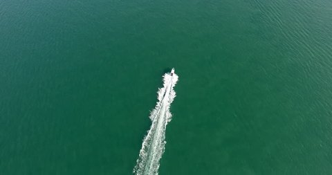 Aerial footage top view with motor boat at high speed cuts the waves while is leaving a long white trail. Conceptual video presentation for tourism. Expensive lifestyle and kind of leisure