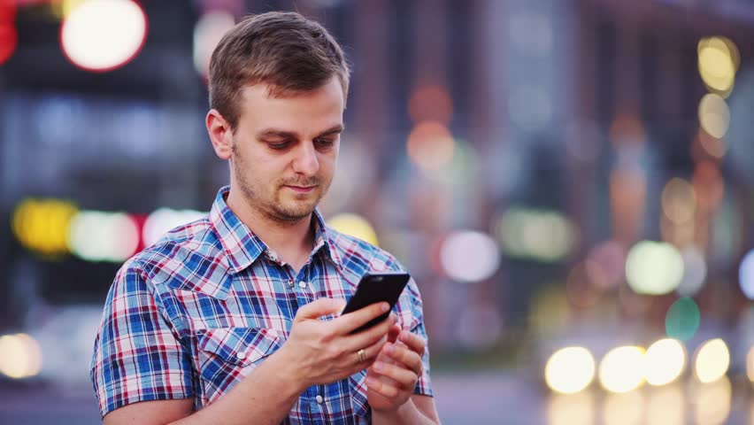 Man using smart phone at night in city. 4K. Handsome young Business Man texting, talking on smartphone outdoors. Professional millennial with cellphone, blurred Night Busy Street lights background. | Shutterstock HD Video #19973587