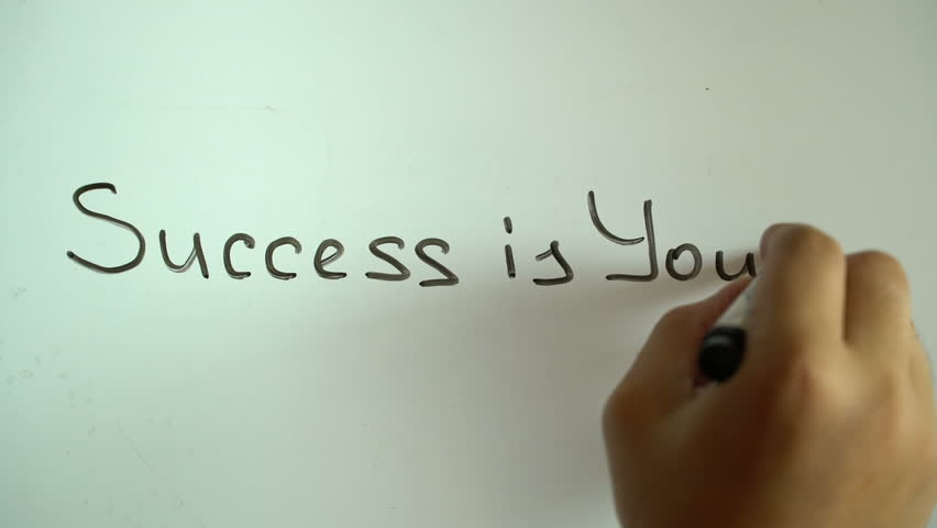 "Hand writing title ""Success is yours"" using a black marker on a white board 