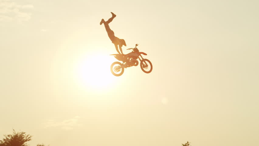 SLOW MOTION: Extreme pro motocross rider riding fmx motorbike, jumping huge jump performing dangerous stunt against the sky. Professional motocross biker jumps big air trick over golden sunset sun
