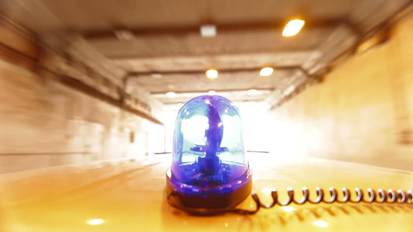Car With Blue Emergency Light Driving Through A Tunnel