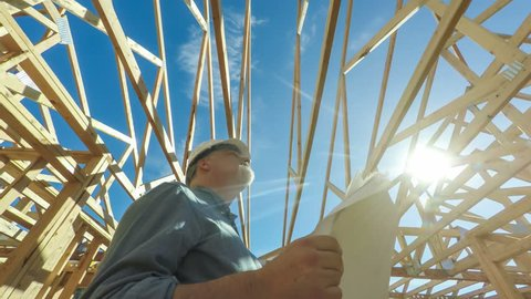 4k clip of a construction worker holding a set of plans, looking up at roof beams of an unfinished residential home