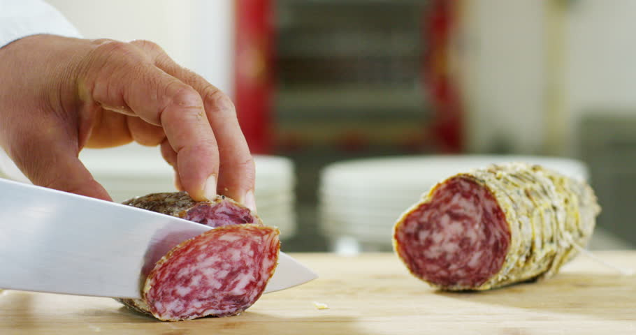 An experienced chef in a professional kitchen cuts the seasoned.Il Italian salami sausage is cut with a professional knife with very thin slices. the concept of nature, Italy, food, diet and bio.