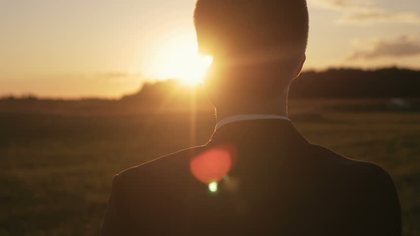Young man looking forward at the sun during the sunrise. Businessman thinking about business planning. | Shutterstock HD Video #20127235