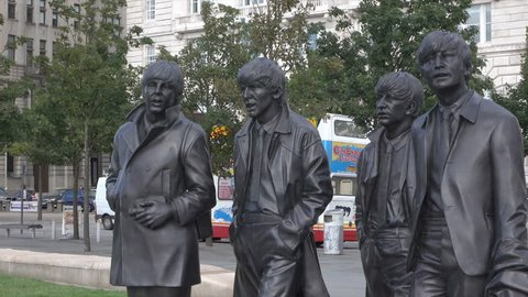LIVERPOOL, MERSEYSIDE/ENGLAND - SEPTEMBER 16, 2016: Tilt up to Statue of The Beatles at Pier Head. The statues were sculpted by Andrew Edwards and donated by the famous Cavern Club where they played.