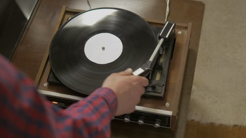 Male hands turning an antiquarian record player on. Man remembering past moments while listening a calm melody at home.