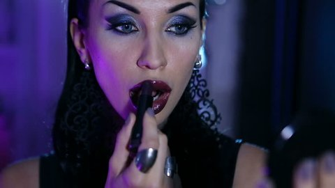 Sexy Woman gets an evening gala Makeup. Woman Preparing for a Nightclub Party. Stylish Sensual vamp Makeup - Smokey Eyes, dark lipstick. High-fashion make-up. Beauty flirting in front of the mirror.