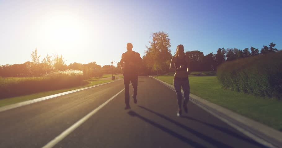 4K shooting: Young couple running in the park. Athletic attractive people jogging in summer enjoying their healthy lifestyle. Front view. Green meadow and forest in the background | Shutterstock HD Video #20153446