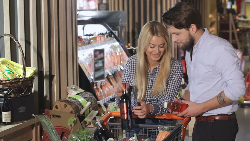 Young couple arguing about the beverage at the mall. Pretty blond woman wanting to buy red wine while bearded man wanting to buy juice. Caucasian man and woman pointing their fingers at the labels on