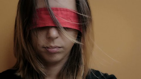 abused woman with eyes blindfolded with red ribbon