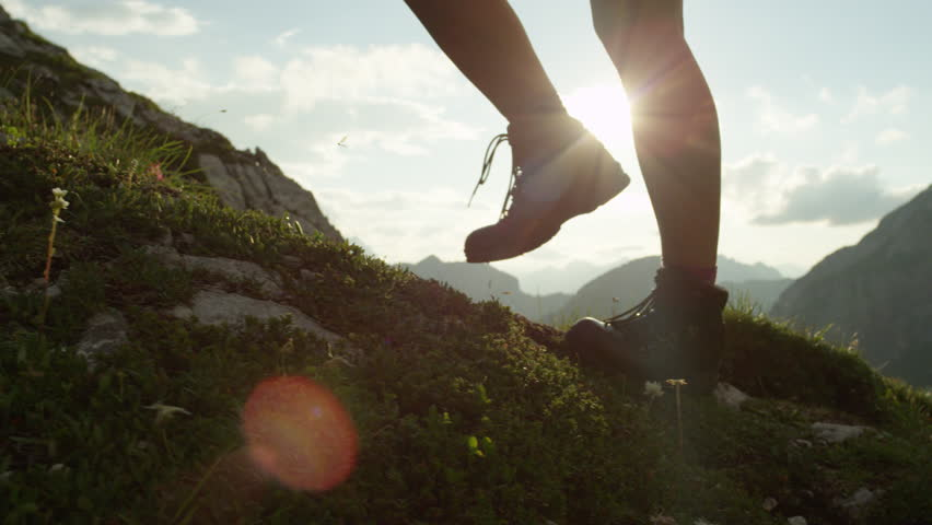SLOW MOTION, CLOSE UP: Detail of vintage leather mountaineering boots and unrecognizable adventurous female hiker climbing mountain peak, hiking uphill on beautiful sunny summer day in European Alps