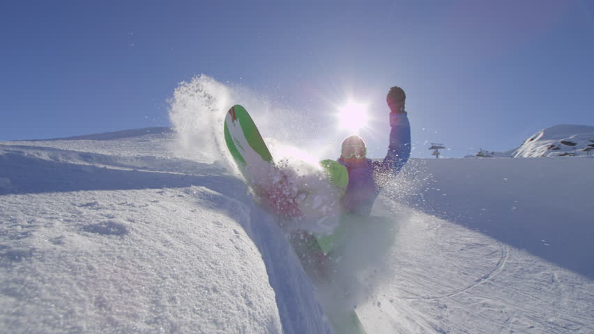SLOW MOTION: Young pro snowboarder riding the half pipe in big mountain snow park, spraying snow into camera on halfpipe wall in sunny winter. Extreme snowboarder snowboarding and doing tricks.
