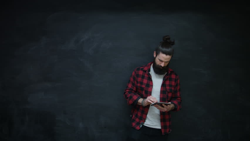 4k thinking hipster man writing in notebook on chalkboard background 4k smiling hipster man using computer tablet looking to side on chalkboard background shot voltagebd Images