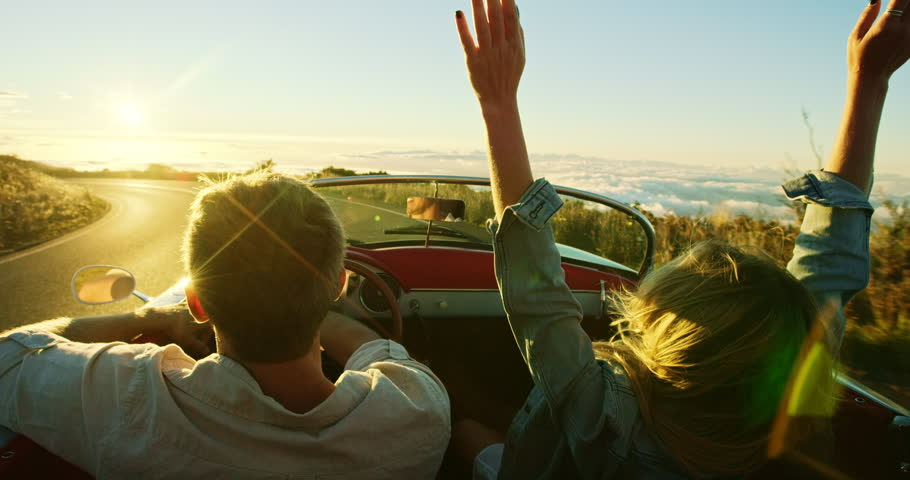 Happy couple driving on country road into the sunset in classic vintage sports car | Shutterstock HD Video #20219026