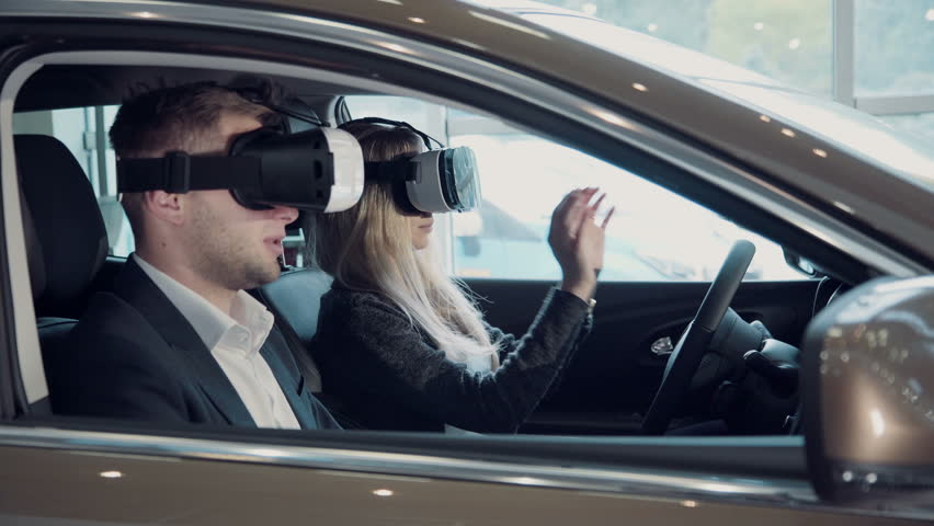 Young woman going for a test drive with the salesman in a new car as she makes a selection for her purchase, or she to pass virtual exam for driver license using virtual reality glasses. | Shutterstock HD Video #20234353