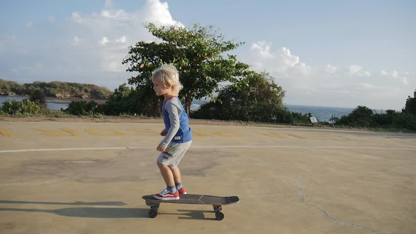 Steadicam shot of cute child skateboarding on helipad in park and giving five on beautiful landscape background with camera lens flare. Having fun with young parents in summer vacation. Slow motion.