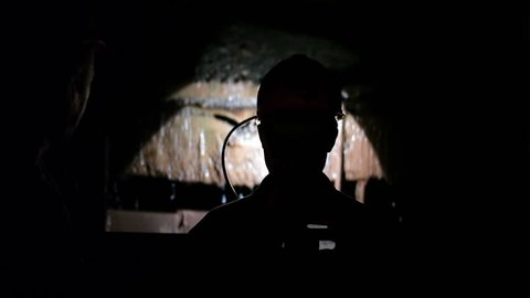 Miner go down into a mine shaft in the elevator cage, silhouette in darkness