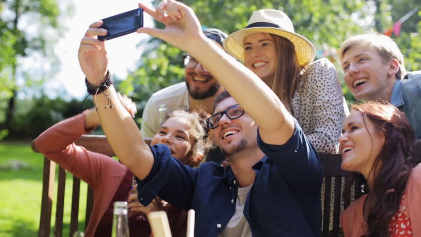 Leisure, party, technology, people and holidays concept - happy friends taking selfie with smartphone and gathering for dinner at summer garden party | Shutterstock HD Video #20265916