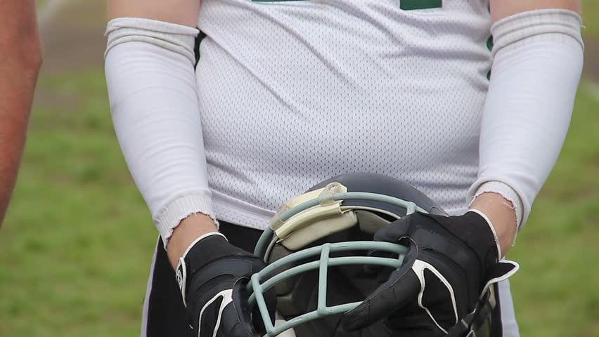 Disciplined football player holding helmet in hands, team preparing for match   Shutterstock HD Video #20269726