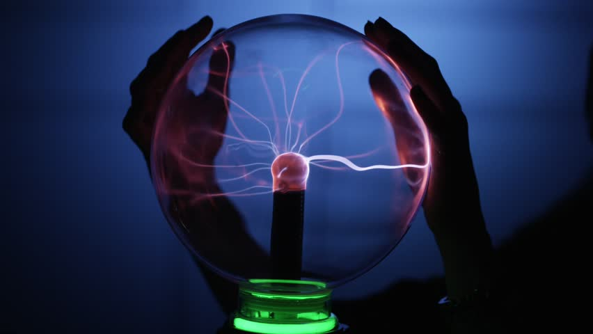 Young woman's hand touching plasma ball