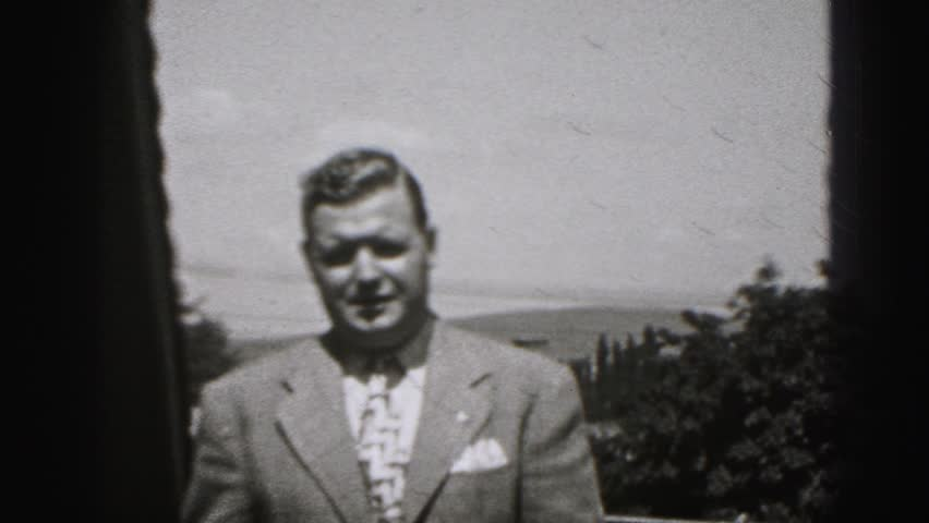 HARRISBURG 1946: a man in a suit and tie walks up to the camera and lifts his eyebrows as he talks #20281366