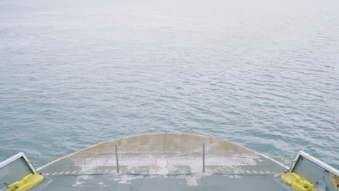 Looking down on the bow (front) of a vehicle transportation ferry as it moves across the sea