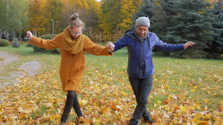 Father teaches daughter dancing in the autumn park. However, they smile and laugh. Many beautiful yellow foliage in the forest.