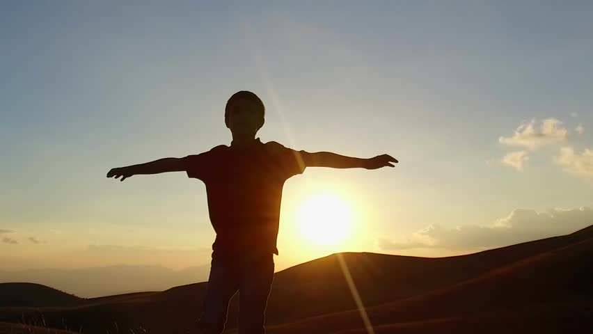 SLOW MOTION: Kid silouette spreading arms and looking to the infinite at the sunset. Conceptual footage.  | Shutterstock HD Video #20355331