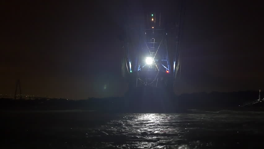 Shrimping trawler sails out to sea at night to fish.