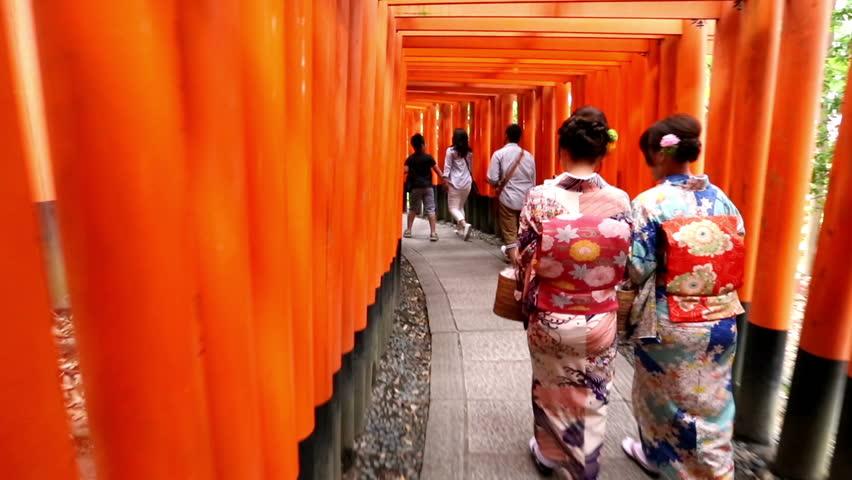 KYOTO, JAPAN - MAY 28, 2016: A women in Japanese geisha style clothing walks through torii gates at Fushimi Inari Taisha in Kyoto, Japan