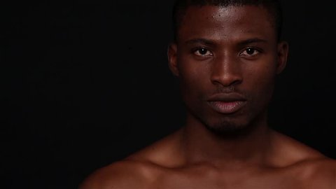 Picture of naked black man posing in studio. Short haired model man with muscular body looking down and up over black background. Fashion or vogue concept.
