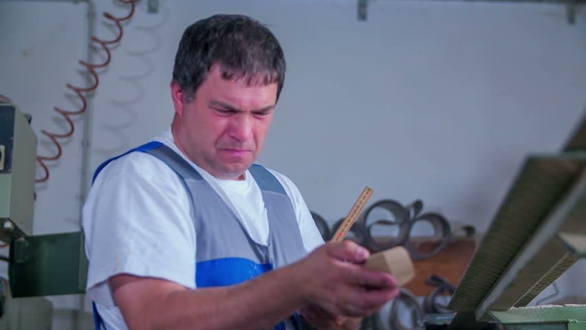 A joiner is trying to measure something with a ruler. He looks very dedicated and focused. Close-up shot. | Shutterstock HD Video #20461456