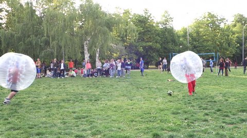 KRASNODAR, RUSSIA – MAY 1, 2016: Young boys playing football in the transparent plastic zorb ball on the grass
