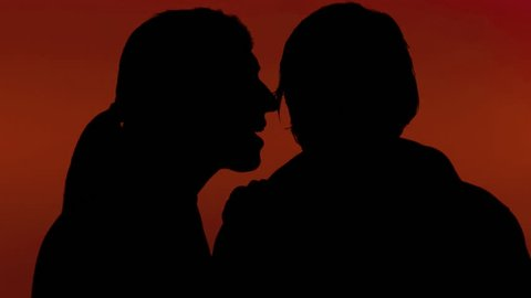 A woman whispering a secret in the ear of a man. Silhouette shot, red background.