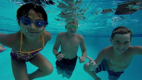 Three kids swimming in pool underwater