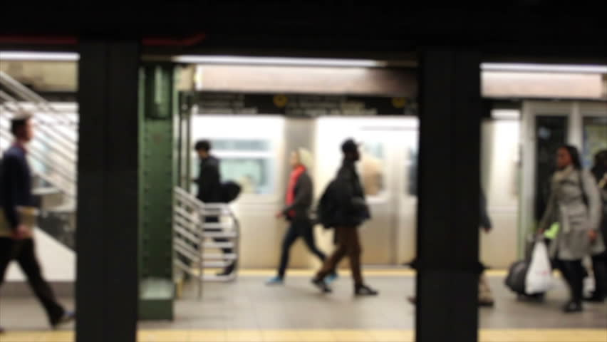 Horizontal HD clip of commuters in a New York subway station, blurred to prevent identification.