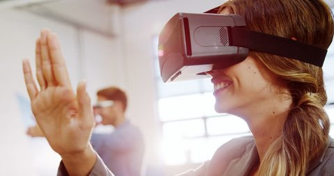 Female business executive using the virtual reality headset at office 4k