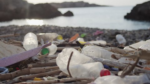 Coastal Pollution. Plastic Litter On A Beach. A Female Passes Right To Left In The Background. Late Summer Afternoon.