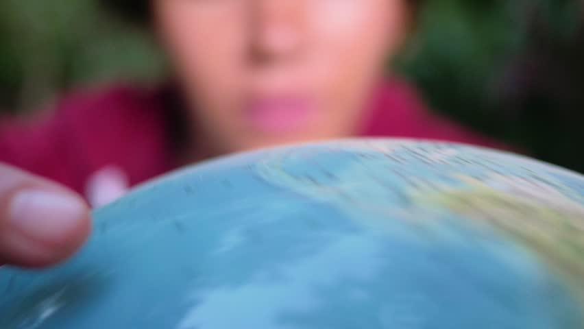 Hispanic woman choosing her next travel site on a spinning globe