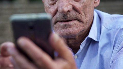 elderly man intent on using mobile phone