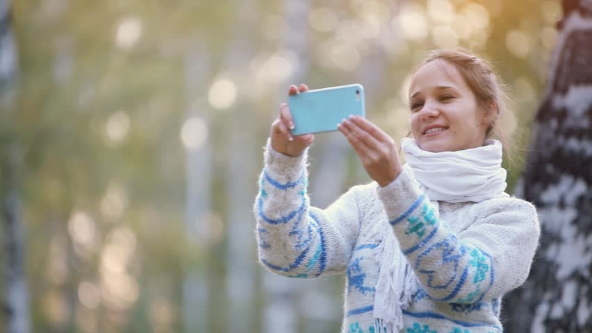 Smiling beautiful woman in a knitted sweater and scarf making selfie with mobile phone in park during the autumn. 1920x1080   Shutterstock HD Video #20557006
