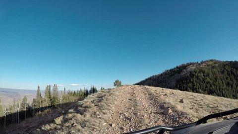 SANPETE, UTAH - OCT 2016: Trail ride 4x4 off road mountain top recreation POV. seasonal Autumn colors exploring high mountain roads trails. sports vehicle UTV side by side 4 wheel drive high ridge.