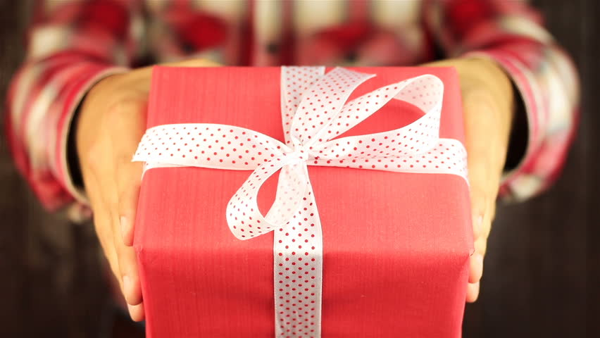 Young man gives a gift on wooden background. Red gift box with white ribbon opening. Congratulate Happy New Year, Merry Christmas, Happy Valentine's Day, presents gifts | Shutterstock HD Video #20586694