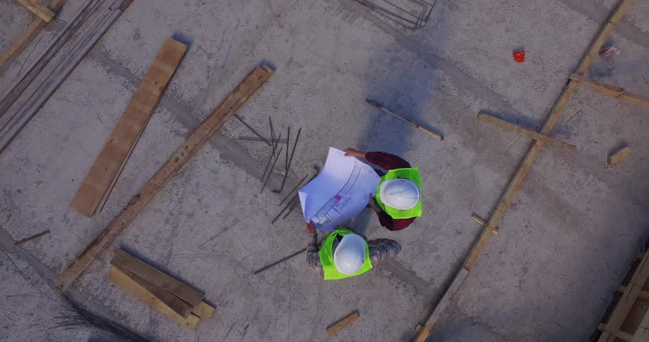 Aerial shot of workers in a construction, structure in the process to be build, tools arround