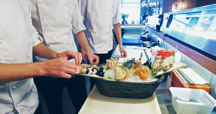 Restaurant Kitchen Video 4k video shooting: three professional chefs prepare sushi set in a